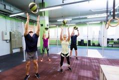 Группа людей с тренировкой шарика медицины в спортзале Стоковые Изображения RF