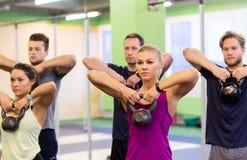 Группа людей с kettlebells работая в спортзале Стоковые Изображения