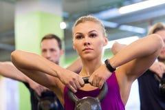 Группа людей с kettlebells работая в спортзале стоковое изображение
