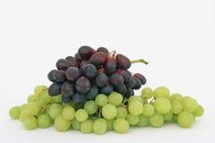 2 группы виноградины на белой предпосылке: зеленые виноградины снизу, черные виноградины на верхней части Стоковые Фотографии RF