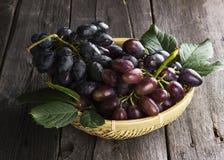 Группы темных виноградин в wattled шаре на деревянной предпосылке Стоковое Изображение RF