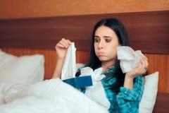 Грустная больная девушка с много бумажных тканей лежа в кровати стоковое изображение