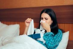 Грустная больная девушка с много бумажных тканей лежа в кровати стоковое изображение rf