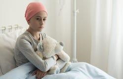 Грустная больная девушка с розовым головным платком обнимая игрушку плюша в больнице стоковые изображения