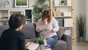 Грустная девушка с расстройством пищевого поведения плача в офисе терапевта держа ткань бумаги