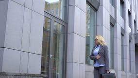 Грустная достигшая возраста женщина смотря отражение стекла окна, идя вдоль офисного здания акции видеоматериалы