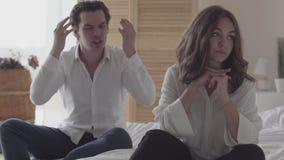 Грустная женщина сидя на кровати на переднем плане пока ее супруг крича на ей на заднем плане Недоразумение внутри видеоматериал