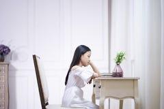 Грустная маленькая азиатская девушка сидит на мысли стола стоковое изображение rf