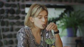 Грустная, подавленная молодая женщина сидя в кафе и выпивая коктейль сток-видео