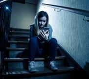 Грустная подавленная несчастная девушка подростка страдая от cyberbullying мобильным умным телефоном сидя самостоятельно стоковая фотография rf