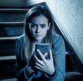 Грустная подавленная несчастная девушка подростка страдая от cyberbullying мобильным умным телефоном сидя самостоятельно стоковое фото rf