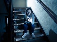 Грустная подавленная несчастная девушка подростка страдая от cyberbullying мобильным умным телефоном сидя самостоятельно стоковые изображения
