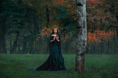 Грустная принцесса с красными белокурыми длинными волосами одетыми в плащ-платье зеленого изумрудного дорогого бархата королевско стоковая фотография rf