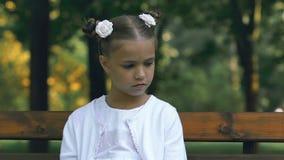 Грустная сиротливая маленькая девочка сидя на стенде в парке, задирать и жестокости в школе видеоматериал