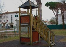 Грустное и сиротливое скольжение, построенное в деревянном, старомодное изолирована спортивная площадка, пустой, без детей зимний стоковые фото