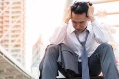 Грустный бизнесмен с костюмом сидя на пути прогулки лестницы в городе после терпеть неудачу проекта дела стоковые фото