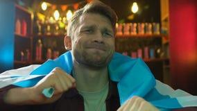 Грустный мужской вентилятор держа флаг Аргентины в баре, разочарованном о терять команды сток-видео