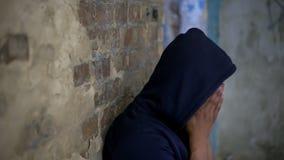 Грустный подросток плача в получившемся отказ доме, жизнь разрушенном войной, скорба и печаль стоковая фотография