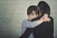 Грустный ребенок обнимая его мать стоковые изображения rf