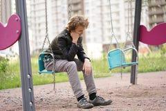 Грустный сиротливый подросток на открытом воздухе на спортивной площадке затруднения отрочества в концепции связи стоковые фото