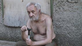 Грустный старый человек попрошайки с тросточкой сидя на улице сток-видео