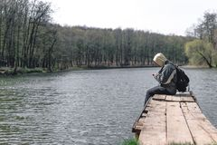 Грустный человек сидит самостоятельно на пристани озером Лес на заднем плане клобук на его голове _ в телефоне владением рук стоковые фотографии rf