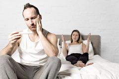 Грустный человек сидя на кровати с беременной женщиной за взглядом на беременном тесте стоковое фото rf