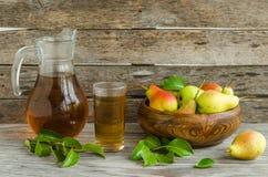Груши в деревянном блюде и carafe сока груши Стоковая Фотография RF