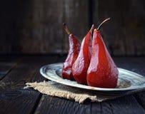 Груши в красном вине на винтажной плите на салфетке на темной деревянной предпосылке Стоковая Фотография RF