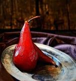 Груши в красном вине на винтажной плите на темной деревянной предпосылке Стоковое Изображение