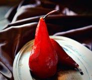 Груши в красном вине на винтажной плите на темной предпосылке ткани Стоковые Изображения
