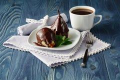 Груши в сиропе карамельки с мятой на белой плите с шоколадом Стоковое фото RF