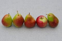Груши и яблоко на таблице Стоковые Фото
