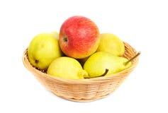 Груши и яблоки в корзине на белой предпосылке Стоковое Фото