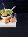 Груши на деревянной доске и зеленых виноградинах в дуршлаге Стоковое Изображение RF