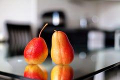 2 груши на стеклянном столе Стоковые Изображения