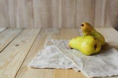 2 груши на linen ткани, деревянном столе Стоковые Изображения RF