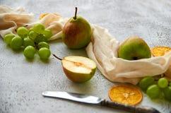3 груши при зеленые виноградины и высушенные части апельсина украшенные с серебряным винтажным ножом и коричневой тканью на серой Стоковая Фотография RF