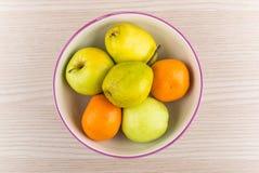 Груши, яблоки и tangerines в стеклянном шаре Стоковые Изображения