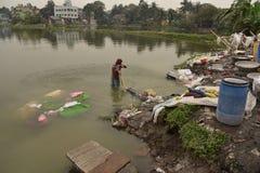 Грязная прачечная: Washerman моет одежды в загрязненной воде стоковые фотографии rf