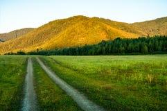 Грязная улица бежит через долину в горах Стоковые Изображения