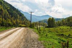 Грязная улица протягивает в расстояние в горах Стоковое Изображение RF