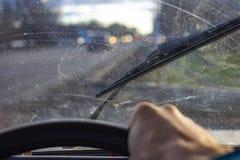 Грязное поцарапанное лобовое стекло автомобиля со счищателем через запачканный руль с рукой водителя на запачканной предпосылке стоковая фотография