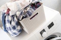 Грязные одежды в пластиковой корзине на прачечной кладут на моя mashine и таблицу b стоковые изображения rf