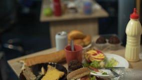 Грязные таблицы вполне нездоровых остатков еды после партии студента в пустой комнате сток-видео