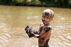Грязный ребенок мальчика смеясь по мере того как он плавает и играет снаружи в реке стоковые фотографии rf