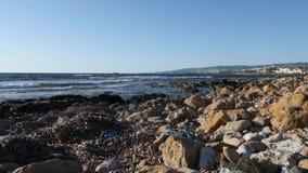 Грязный скалистый пляж заполненный с пластиковыми бутылками и бумажной поганью Куча погани на пляже, видеоматериал