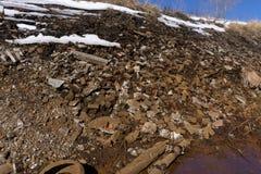 Грязь и лужицы на грязной улице Горящая свалка мусора на заднем плане стоковые изображения rf