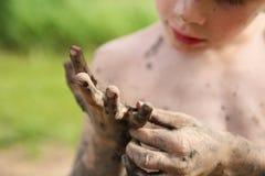 Грязь рудоразборки мальчика с его пакостных рук стоковые изображения rf