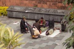Гуанчжоу, Китай - 15-ое марта 2016: нескольк бродяги играя карточек на улице Стоковое Изображение RF